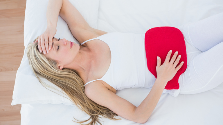 woman with hot water bottle, 'It burns when I pee, what now? The GP's guide by healthista.com