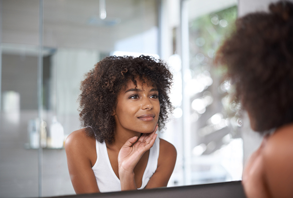 woman-looking-at-self-in-a-mirror-13-positive-affirmations-to-make-you-more-successful-in-life-healthista