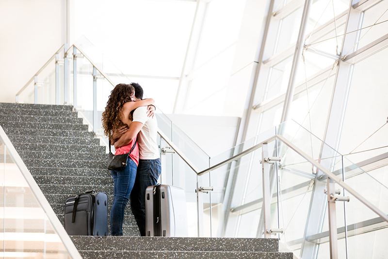 couple-hugging-on-stairs-with-luggage-8-challenges-long-distance-relationships-face-and-how-to-overcome-them-from-Milena-Nguyen-Healthista