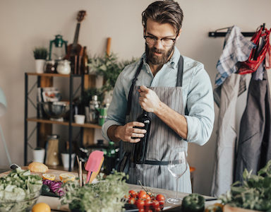 guy-with-wine-bottle-how-jusrt a splash to-cook-healthy-with-alcohol-featured-by-healthista