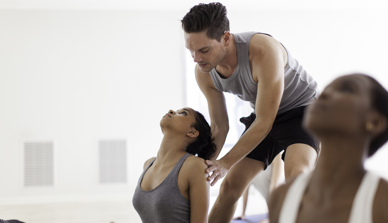 Yoga instructor helping his learner with a yoga pose