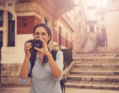 21 solo travel secrets - woman with camera - featured