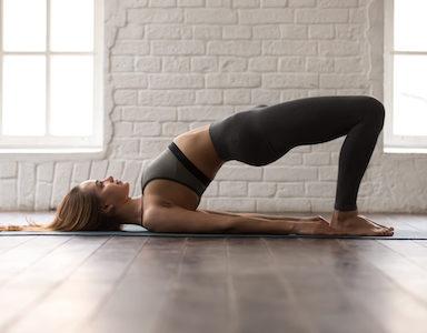 Woman practicing yoga, Glute Bridge exercise, dvi pada pithasana pose