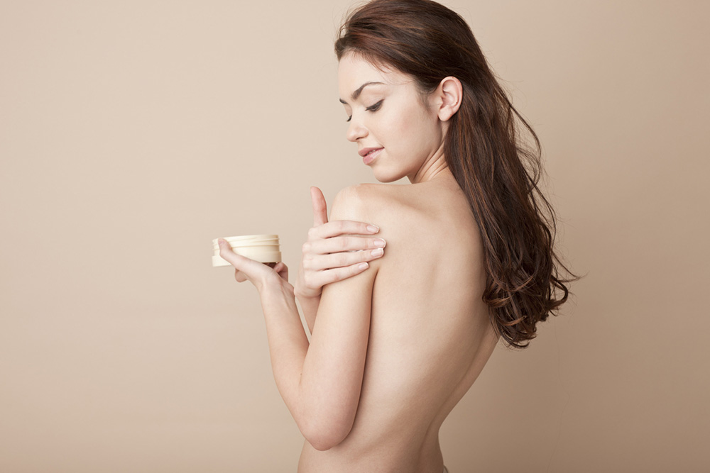 4-ways-stress-is-showing-on-your-skin-and-exactly-how-to-cope-woman-applying-moisturisor.jpg