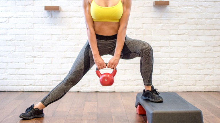 leg workout with kettlebells woman-doing-squats-with-kettle-bell-healthista