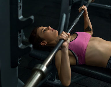 woman-doing-a-barbell-bench-press,-gym-basics-series-by-healthista.com