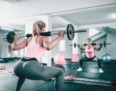 woman squating with bar post featured squats healthista
