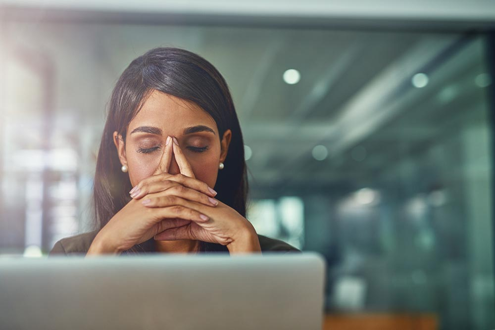 bad-habits-woman-under-pressure-at-work-sat-in-front-of-her-computer.jpg