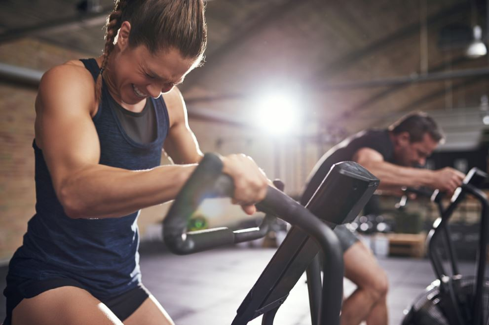 Woman on assault bike avoid gym injuries