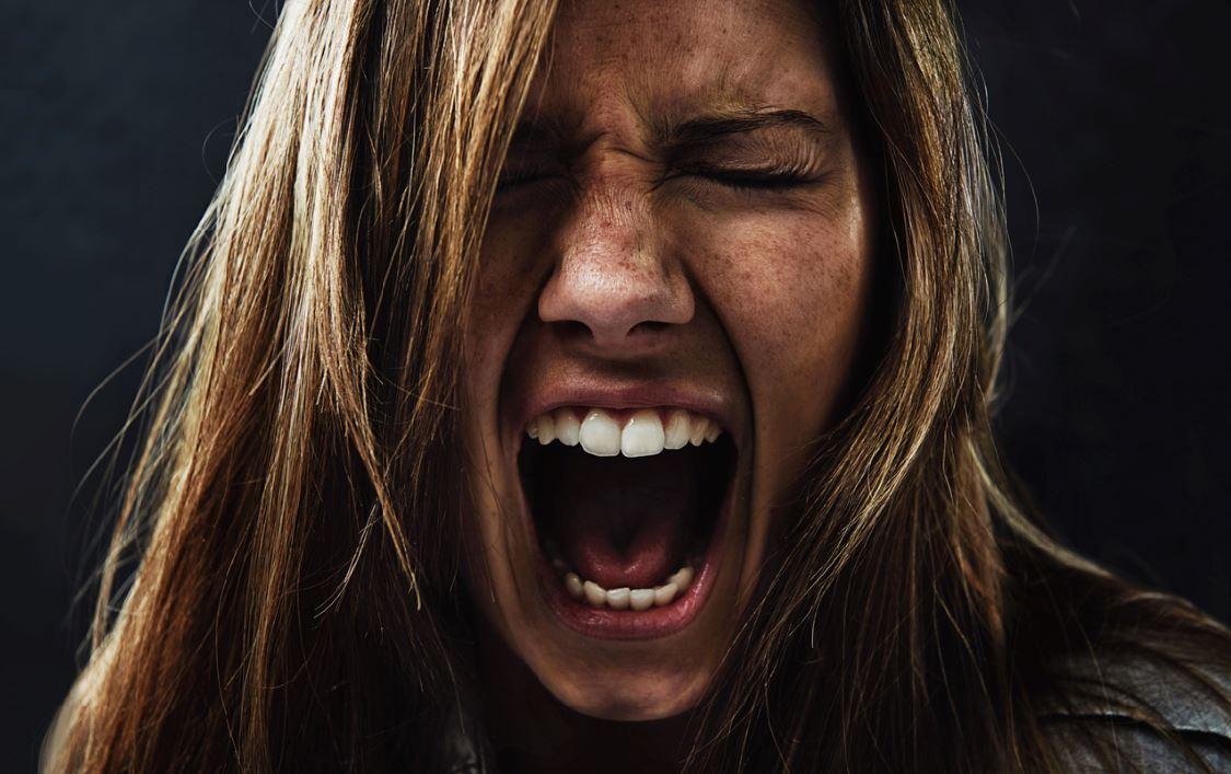 stressed woman migraine symptoms