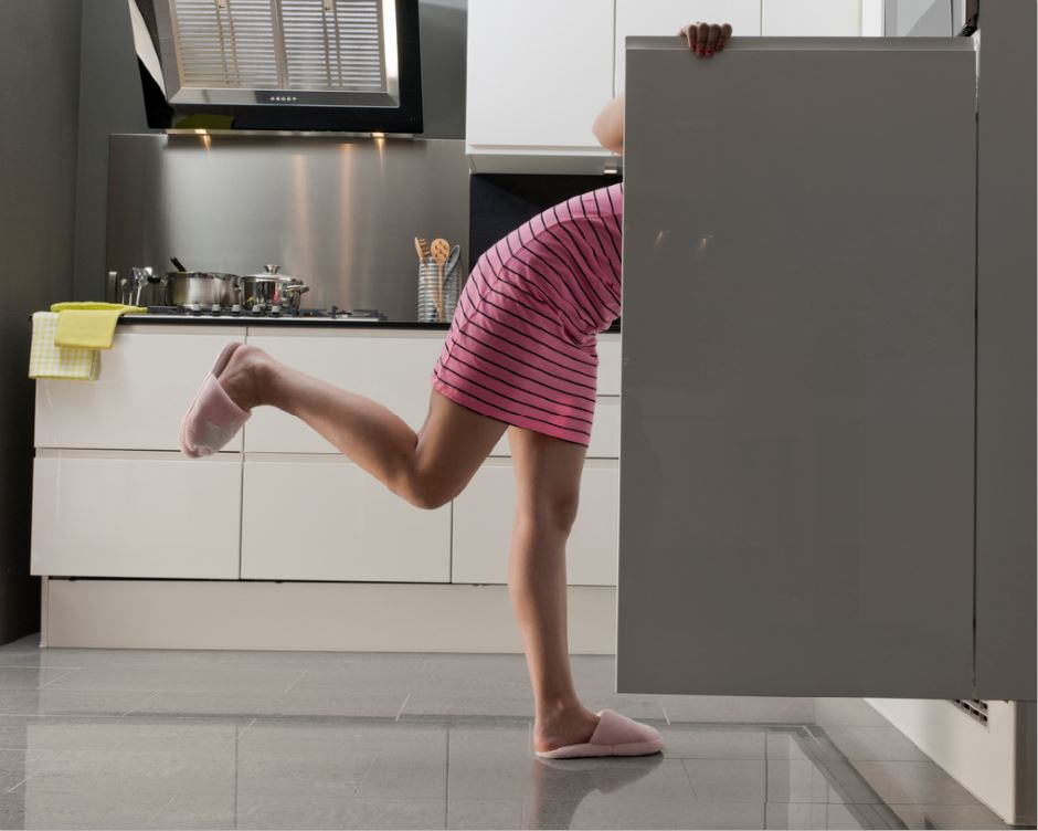 woman in her fridge looking for a snack bad habits