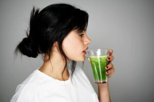 5 ways to detox your body naturally this summer woman drinking green detox juice