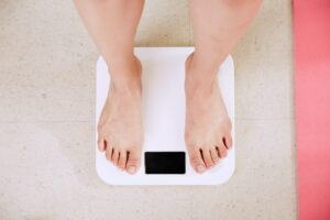 4 ways you can change your relationship with exercise woman stood on scales