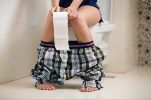woman sat on toilet weak bladder