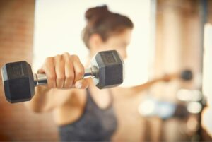6 strength training benefits everyone should know about woman lifting weights at gym dumbbells