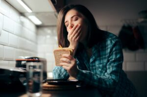 Tired of being tired all the time 7 tried and tested ways to improve your snooze woman eating sandwich at night
